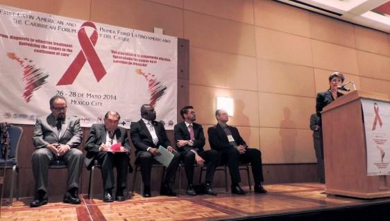 Mercedes Juan en un Podium al fondo representates de organizacipnes escuchando