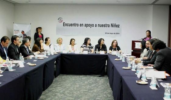 Personas sentadas en una mesa en forma de herradura al fondo un anuncio con el texto Encuentro en apoyo a nuestra niñez