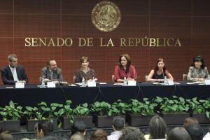 Grupo de personas sentadas en una mesa arriba de ellas la palabra Senado de la República