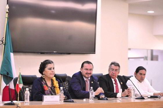 Antonio Sansores Sastré en sentado con un microfono acompañado de tres personas