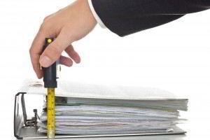 Una carpeta con documentos siendo medida con cinta metrica