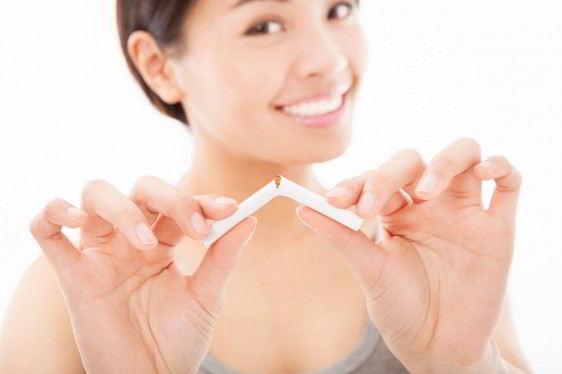 Acercamiento a un cigarro roto en las manos de una mujer sonriendo