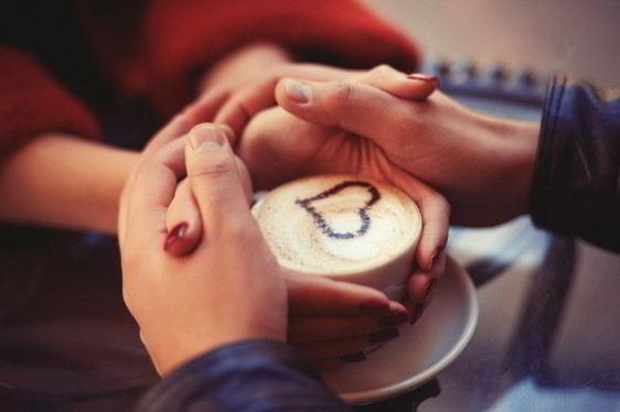 cuatro manos envuelven alrededor de una taza de café con una figura de corazón