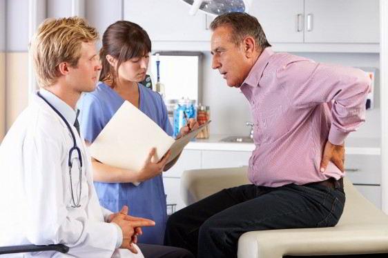Adulto mayor se toca la espalda médico lo observa al lado de una enfermera se encuentran en un consultorio médico
