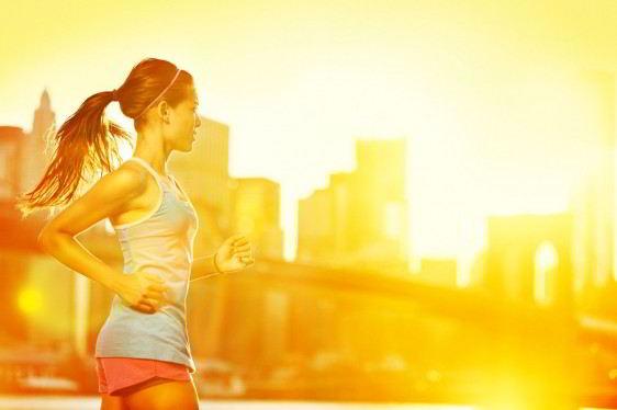 Mujer corriendo con una puesta de sol naranja