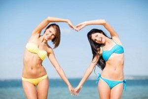 Dos mujeres en la playa haciendo con su cuerpo un corazón