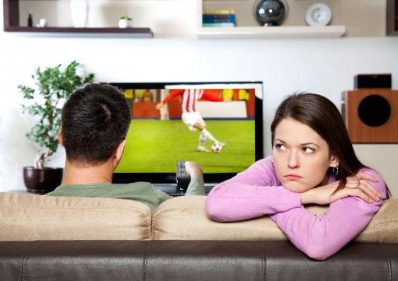 mujer aburrienda, mientras su compañero viendo deporte