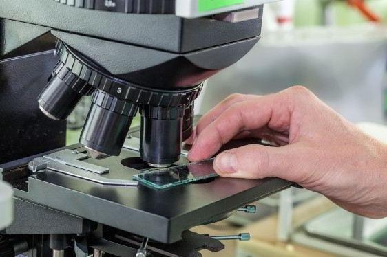 Acercamiento a microscopio persona insertando una muestra