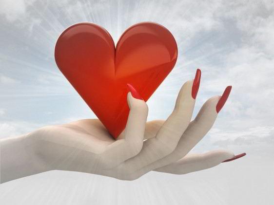 Acercamiento a la mano de una mujer que sostiene un icono de corazón en la mano atrás un cielo azul