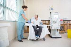Enferemera con paciente al lado de un aparato de dialisis