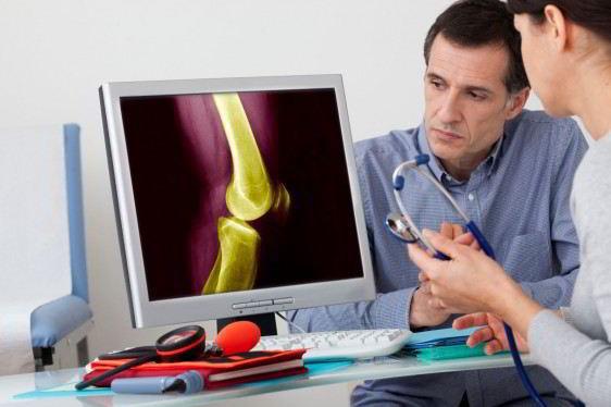 Una doctora observa una pantalla con simulación de huesos el paciente al fondo escucha