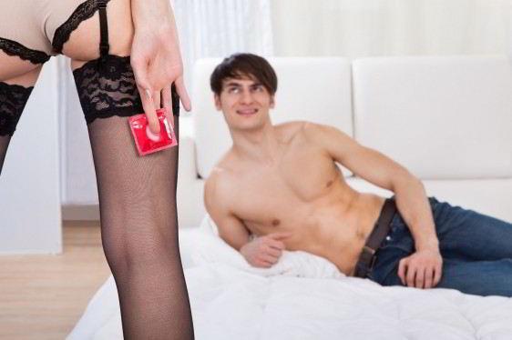Sección media de una mujer en medias sosteniendo un condón