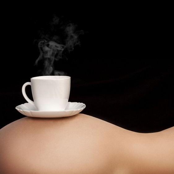 Taza de café en el torso de una mujer en fondo negro