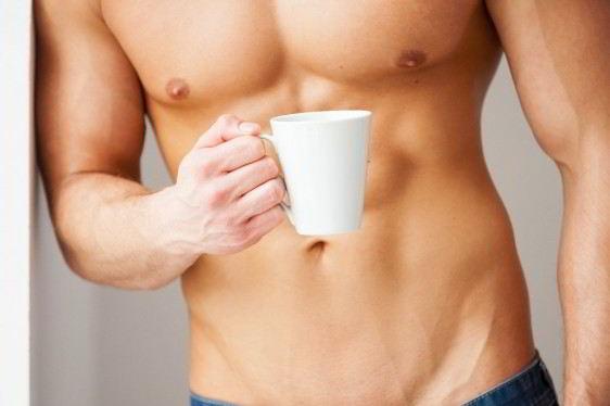 Acercamiento al pectoral de un hombre musculoso con taza de café