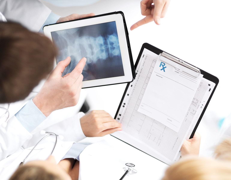 Acercamiento a las manos de profesionales de la salud que sostienen un documento y una computadora tablet