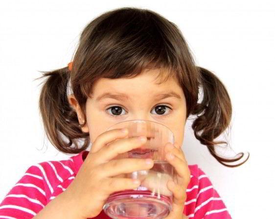 Niña pequeña von trenzas y camisa rosa con rayas blanca bebiendo un vaso con agua