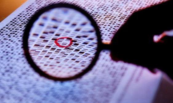 Acercamiento a una diapositiva con genes y una mano sostiene una lupa sobre una secuencia marcada con circulo rojo