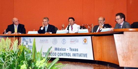 """Grupo de personas sentadas en u amesa abajo un letrero con el texto """"México - Texas TABACO CONTROL INICIATIVE"""""""