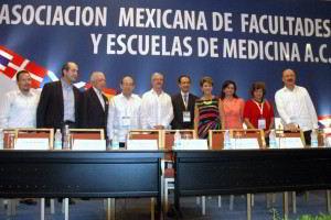Personas de pie atras un letrero con e texto Asociación Mexicana de Facultades y Escuelas de Medicina