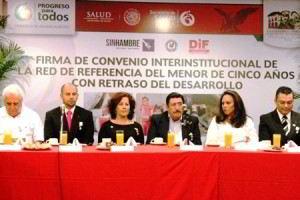 Grupo de funcionarios sentados en una mesa atras un letrero con el texto convenio de Red de Referencia y Contrarreferencia de la Estrategia de Desarrollo Infantil