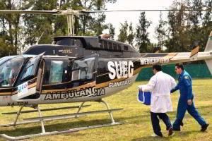 Dos personas caminando a un helicóptero una de ellas carga una caja azul