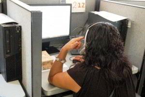 Telefonista viendo una pantalla de computadora con audifonos