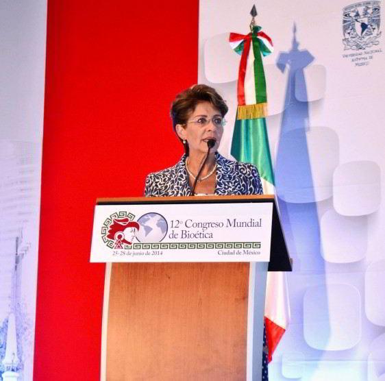 """Mercedes Juan, de pie en un podium con un letrero con el texto """"12 Congreso Mundial de Bioética"""" la bandera de México en el fondo"""