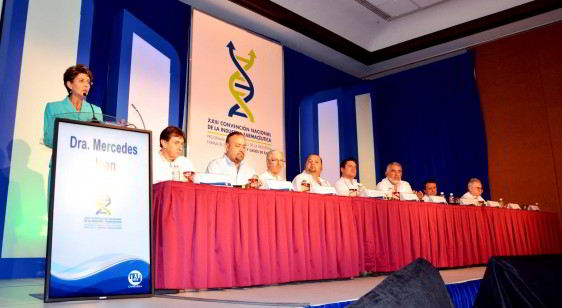 """Personas sentadas en una mesa Mercede Juan de pie en un podium atras un letrero """"XXIII Convención Nacional de la Industria Farmacéutica"""""""