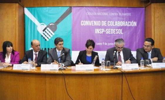 Grupo de personas sentasa en un escritorio firmando documentos