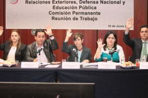 Senadores sentados en una mesa con mano en alto
