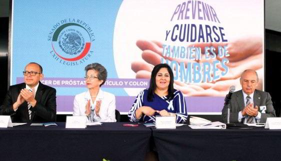 """Personas sentadas en una mesa con letrero con texto """"PREVENIR Y CUIDARSE TAMBIEN ES DE HOMBRES"""""""
