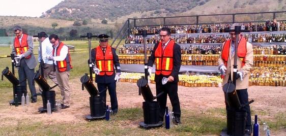 Funcionarios destruyendo envases con bebidas ilegales