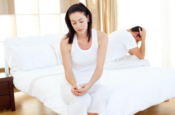 Mujer sentada en cama observando prueba de embarazo al fondo un hombre cabizbajo