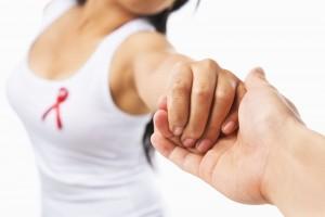 Mujer dando la mano a otra en el pecho con un listón rojo