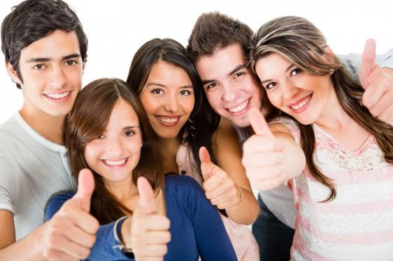 Grupo de amigos mostrando sus dedos pulgares hacia arriba
