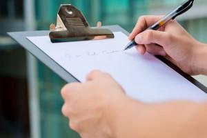 Persona escribiendo sobre una tabla con sujetador de documentos
