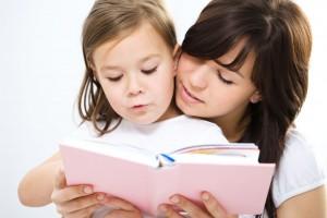 Madre recargada con hija que se encuentra leyendo