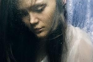 Mujer mirando la lluvia en una ventana