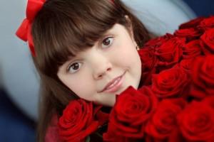 Acercamiento al rostro de una niña con un moño rojo y rosas rojas en sus manos