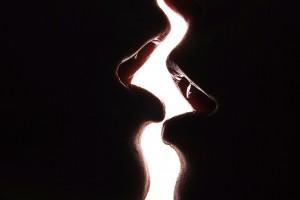 Acercamiento a los labios de dos mujeres besándose en un fondo blanco
