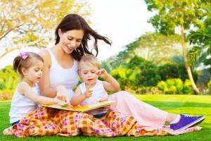 Mujer con niños en el campo leyendo