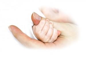 Acercamiento a la mano de una mujer con un bebe agarrando su dedo pulgar