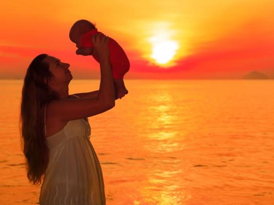 Silueta de mujer cargando un bebé con sus manos al fondo un amanecer naranja