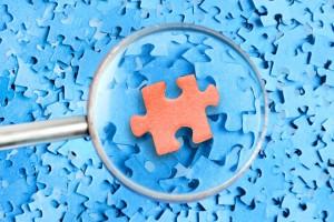 Lupa sobre piezas de rompecabezas azul destaca pieza roja