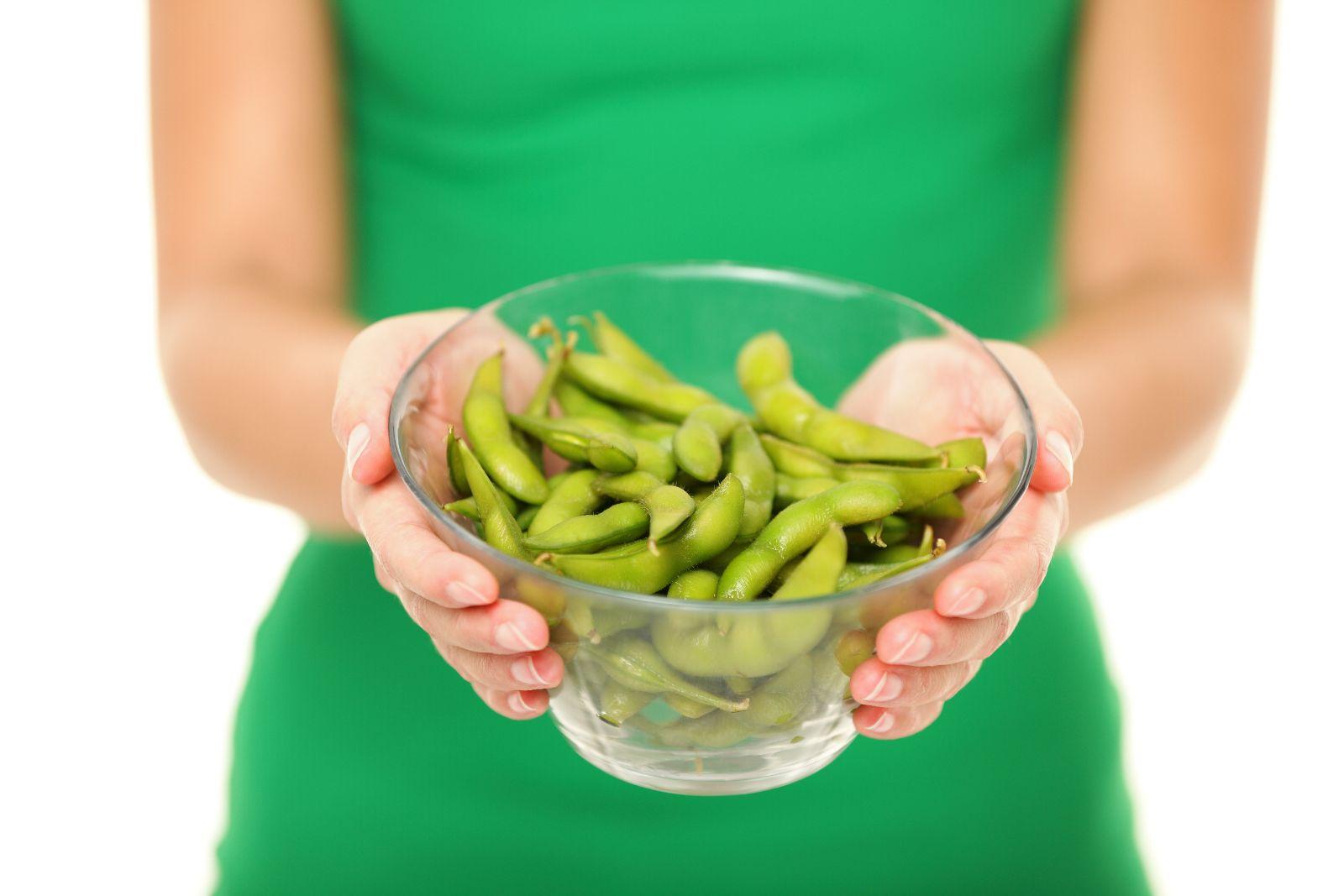 Acecamiento a las manos de una mujer con vestido vede que sostiene un recipiente con bayas de soya