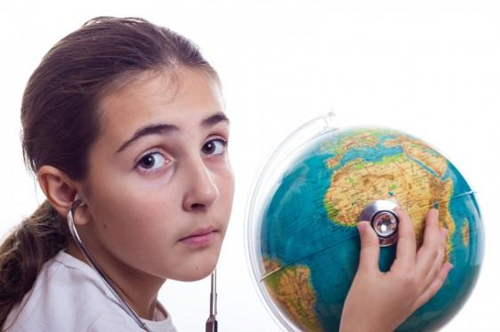Niña escucha con estetoscopio a un globo terraqueo
