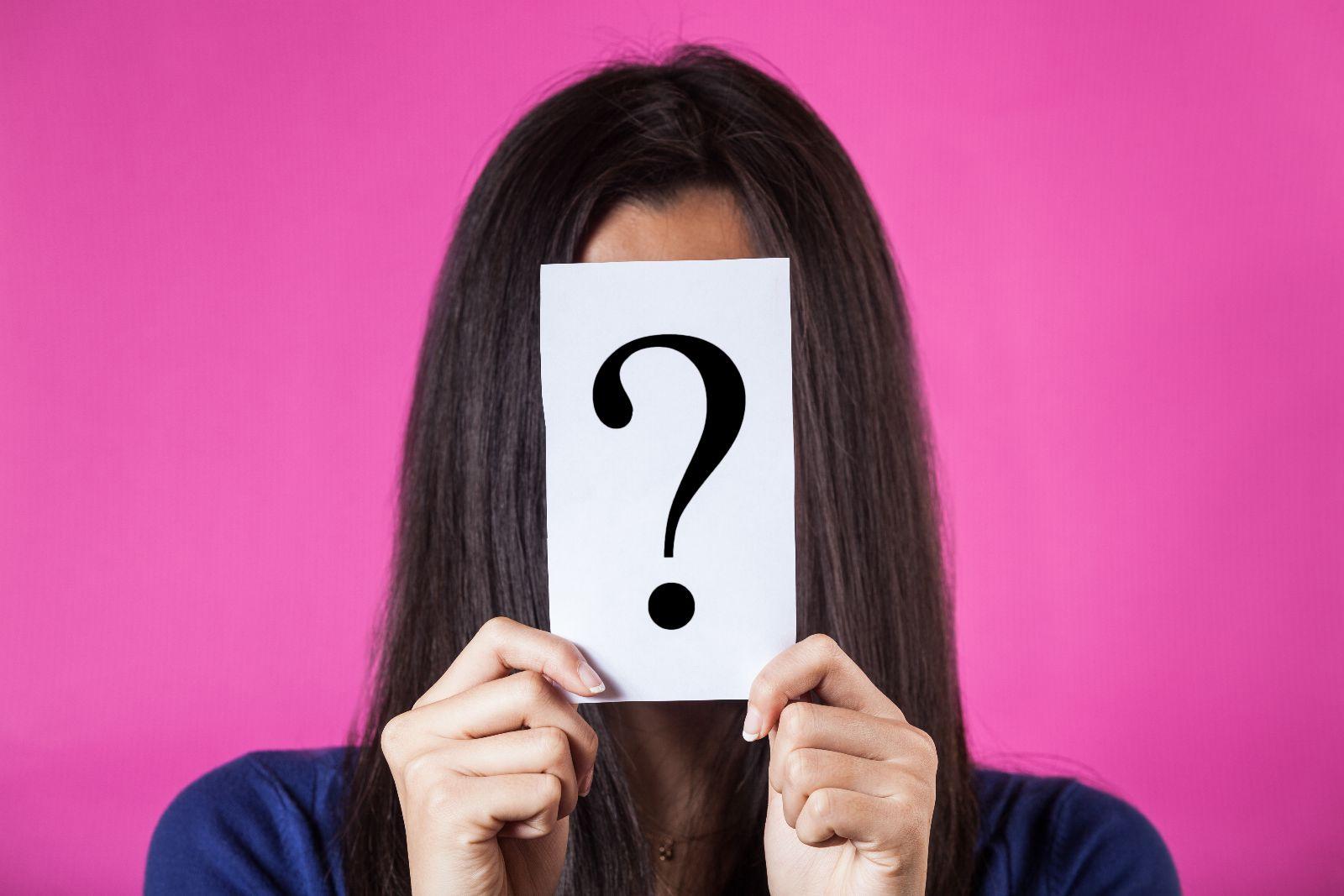 Mujer sostiene enfrente de su rostro hoja con signo de interrogación