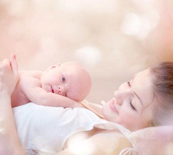 Mujer acostada abrazando a un recién nacido