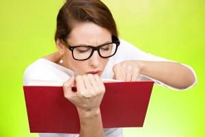 Mujer usando lentes con un libro muy cerca de sus ojos