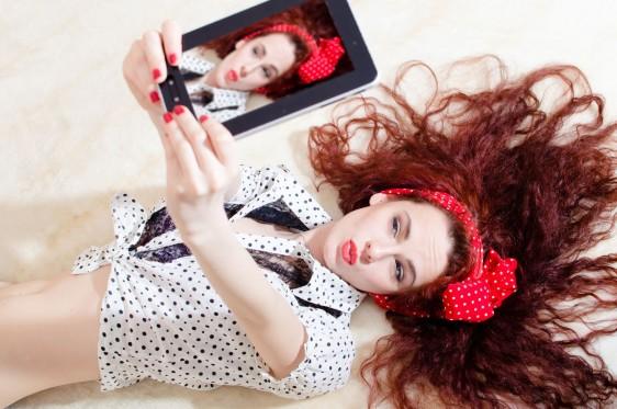 Mujer tomándose una fotografía con una tablet